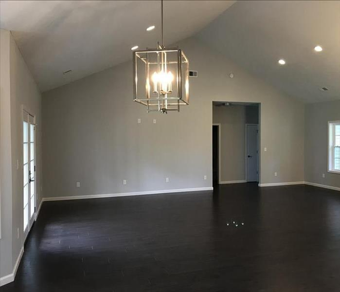 Clean and empty living room with hard wood flooring and new hanging lantern