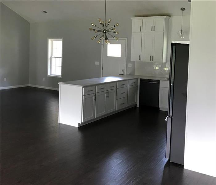 Clean and restored entry way, white cabinets & wood flooring.
