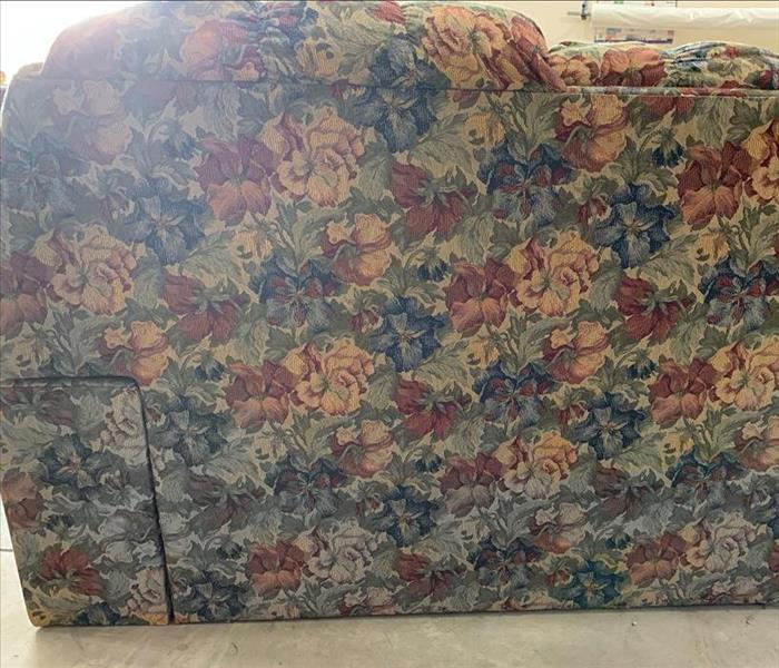 Floral couch with gray water stain at the bottom